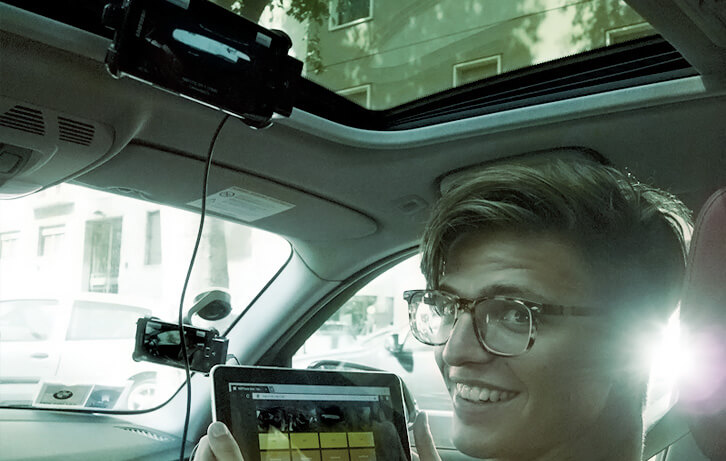 Marco in the car, holding the tablet through which he made the director